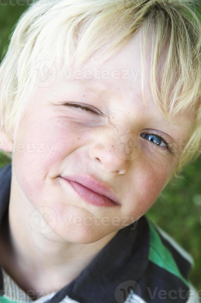 ung pojke som blinkar ett öga. foto