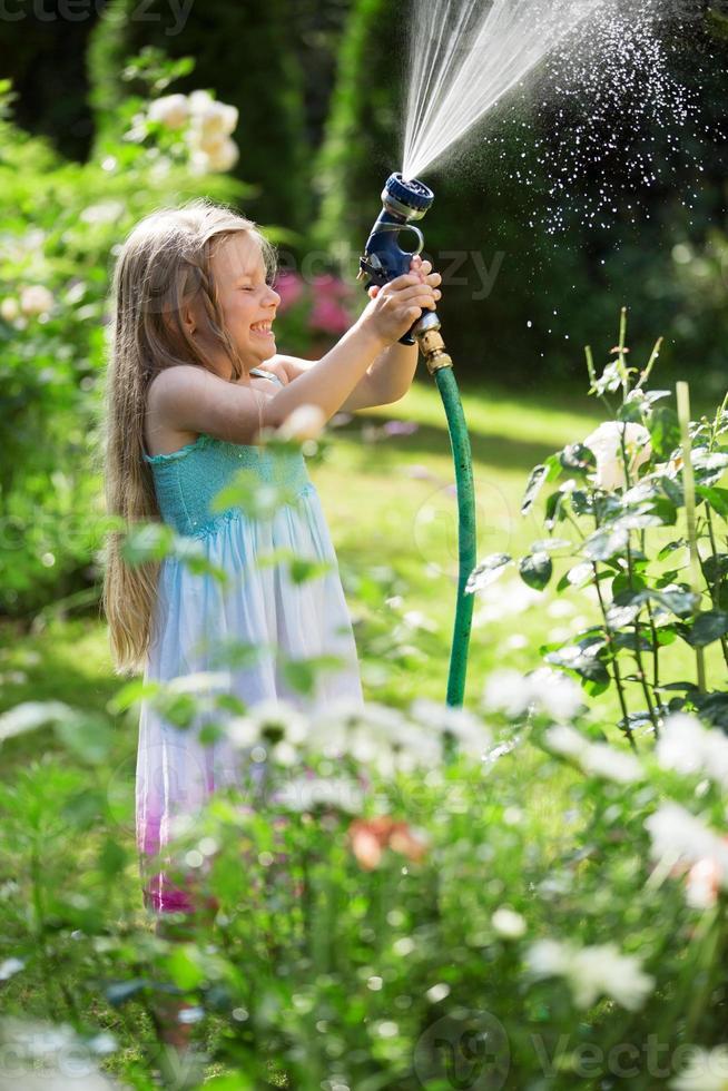 flicka vattna växter med trädgårdsslang foto