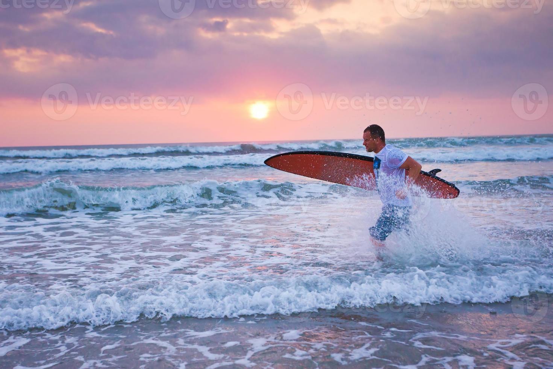 surfare som körs på kusten i Indonesien foto
