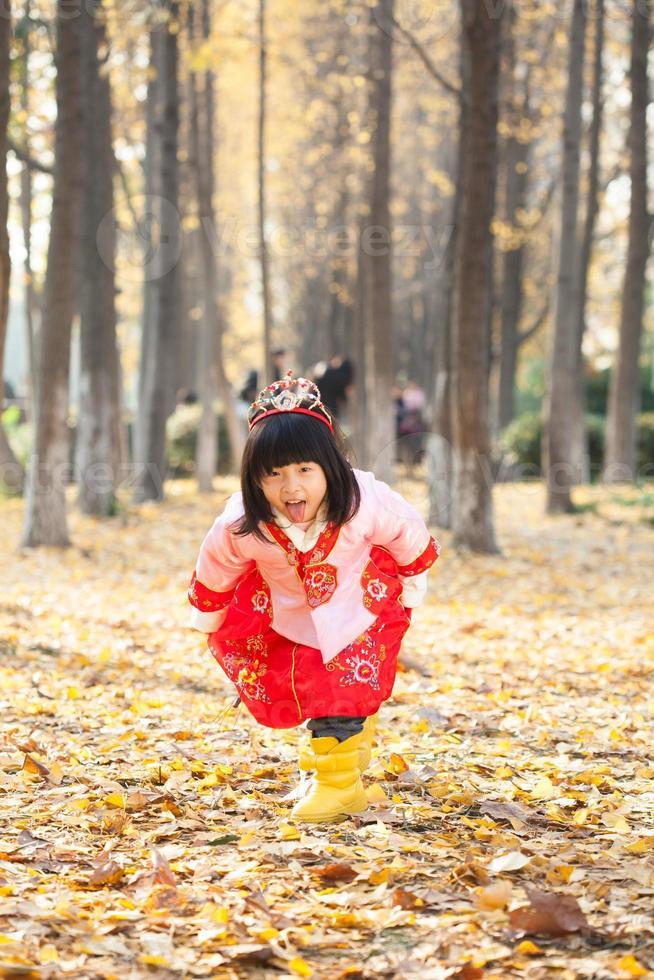 liten flickaklänning i snövit dräkt i skogen foto