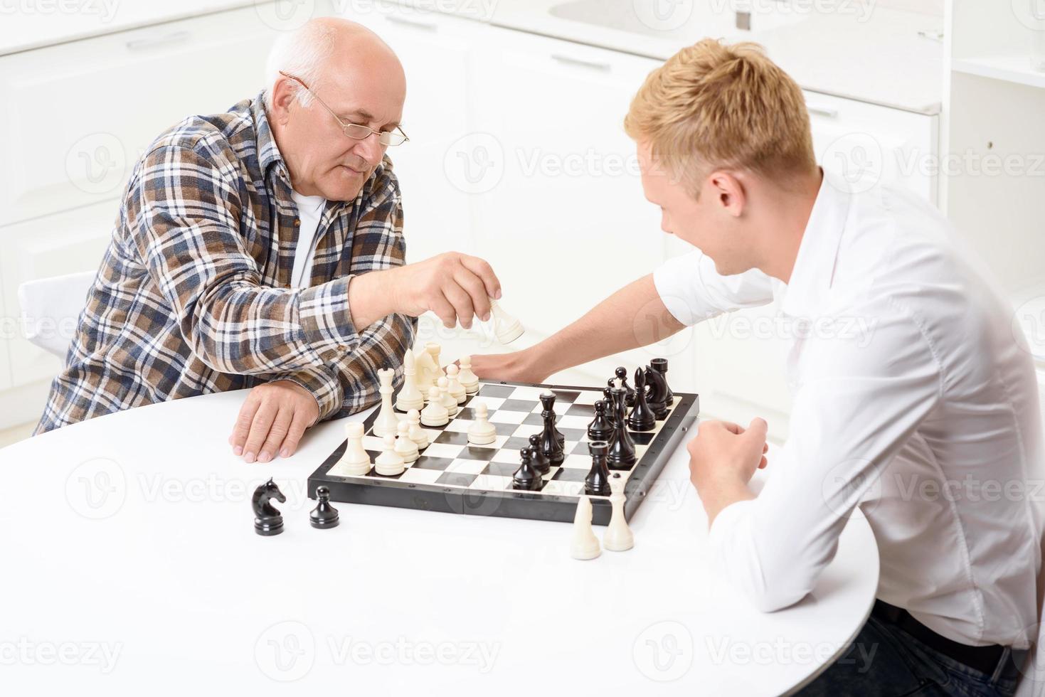 barnbarn och farfar som spelar schack i köket foto