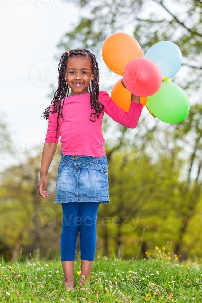 utomhus porträtt av en söt ung liten svart flicka som spelar foto