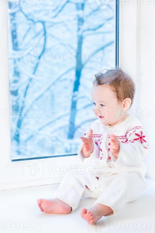 söt liten baby i stickad tröja med snöflingaprydnad foto