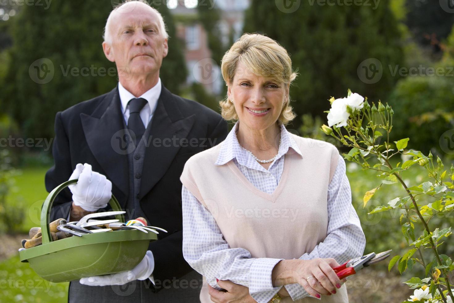 kvinna med sekatörer av butler med korg med trädgårdsredskap foto