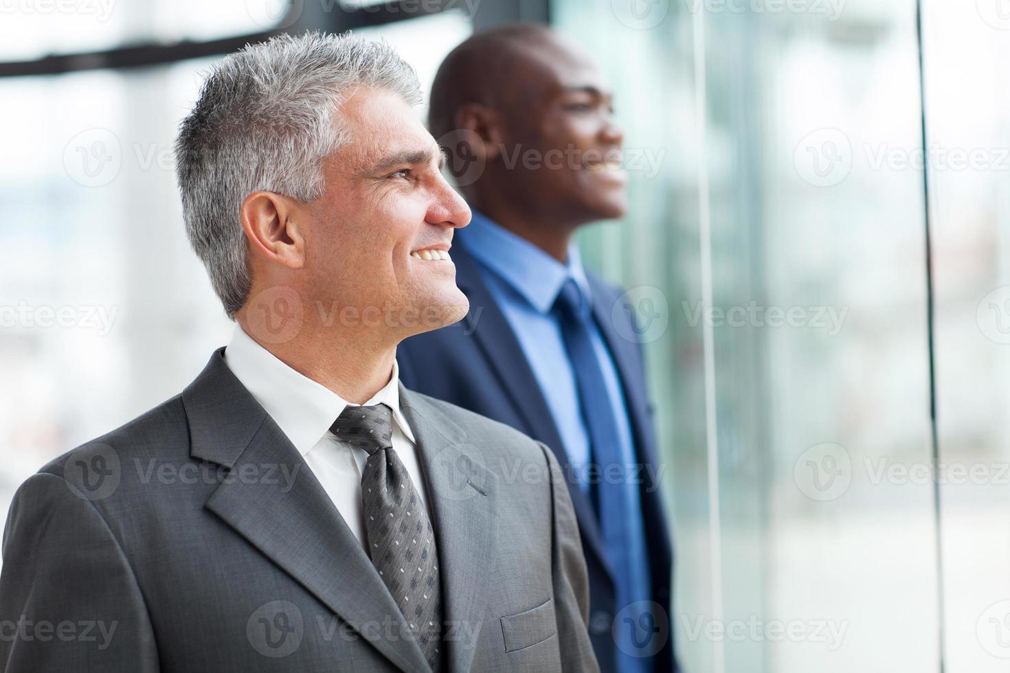 två affärsmän som tittar ut genom fönstret foto