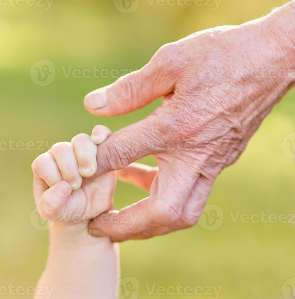 händer gammal man och ett barn foto