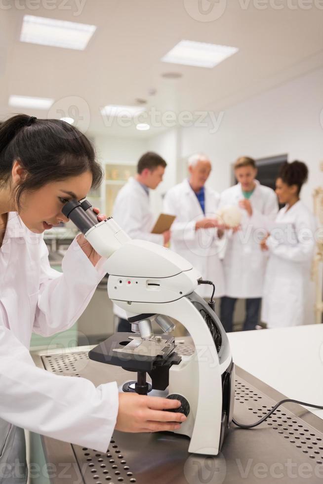 ung medicinsk student som arbetar med mikroskop foto