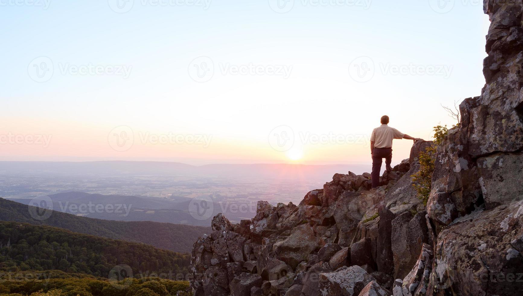 äldre man tittar på soluppgång över blå ås foto