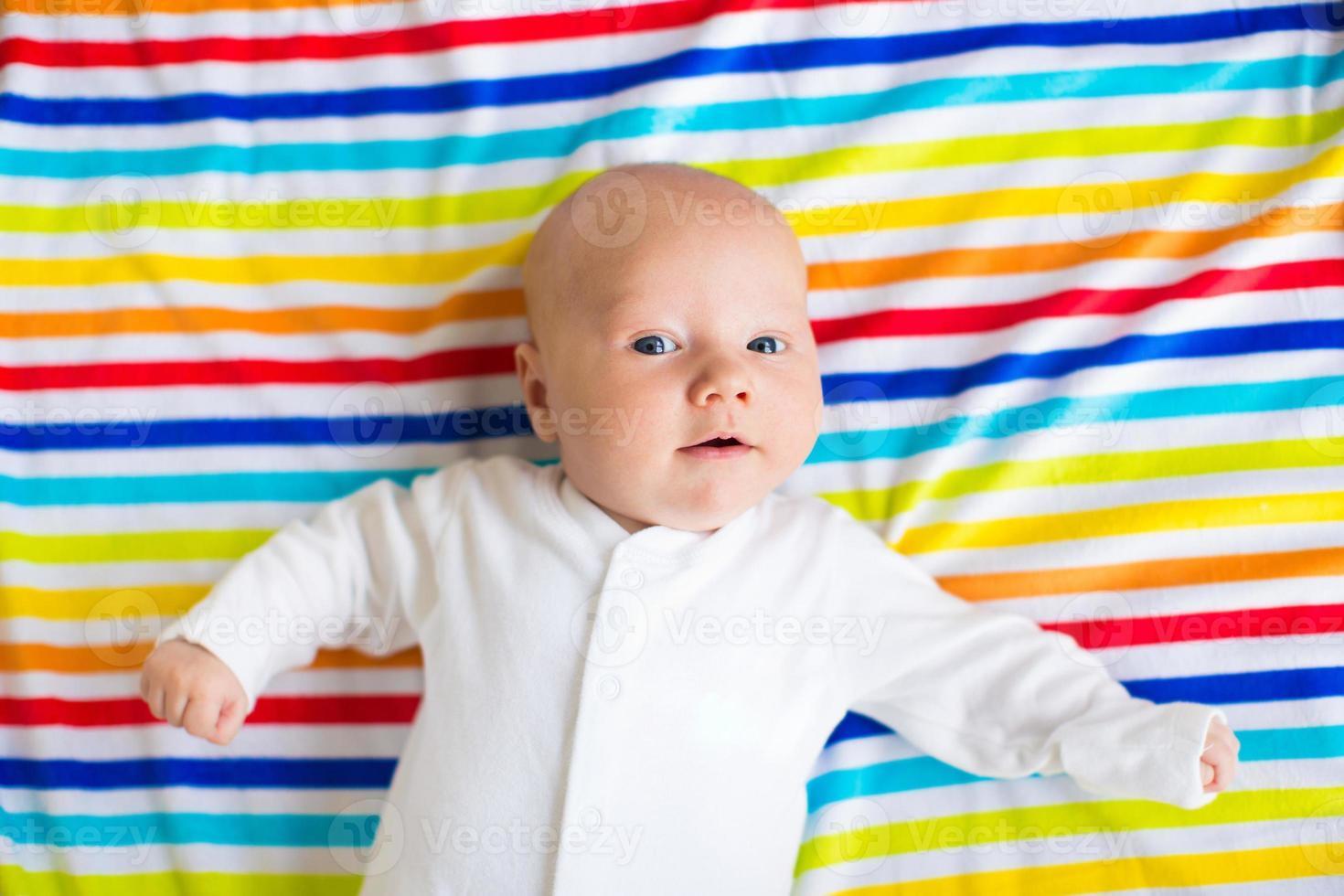 söt baby på en färgglad filt foto