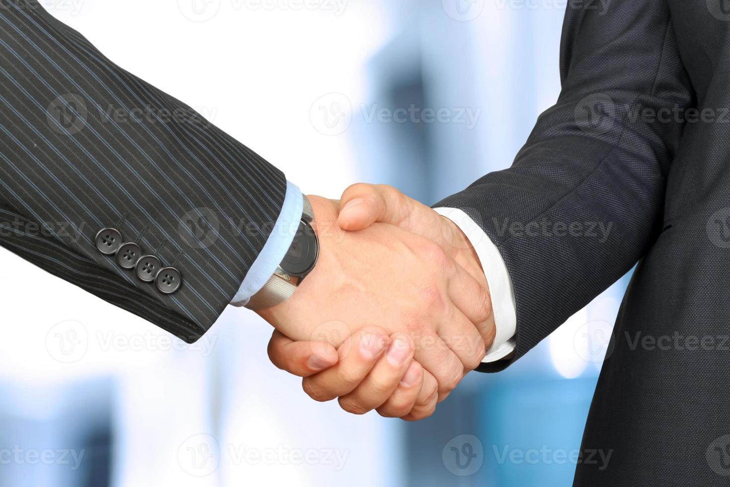 närbild av en fast handskakning mellan två kollegor utanför foto