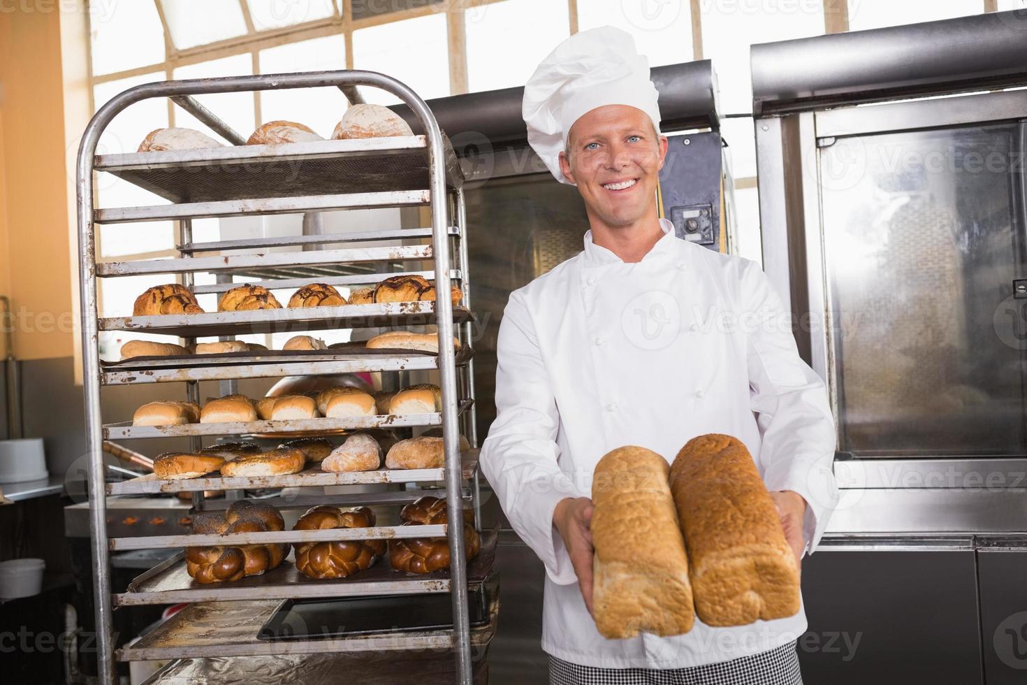 leende bagare som visar bröd foto