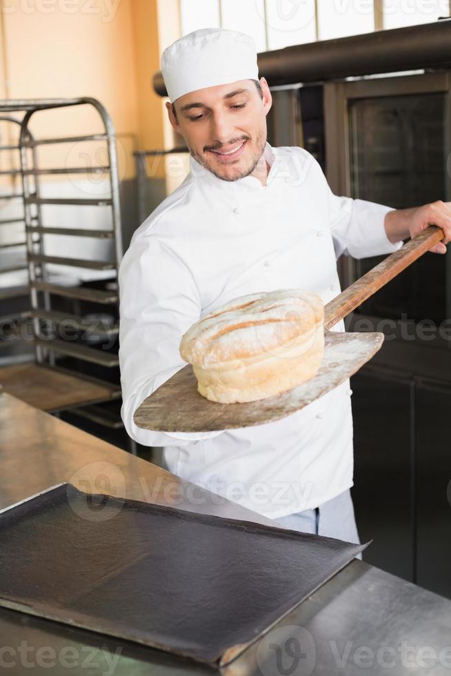 glad bagare som tar ut färskt limpa foto