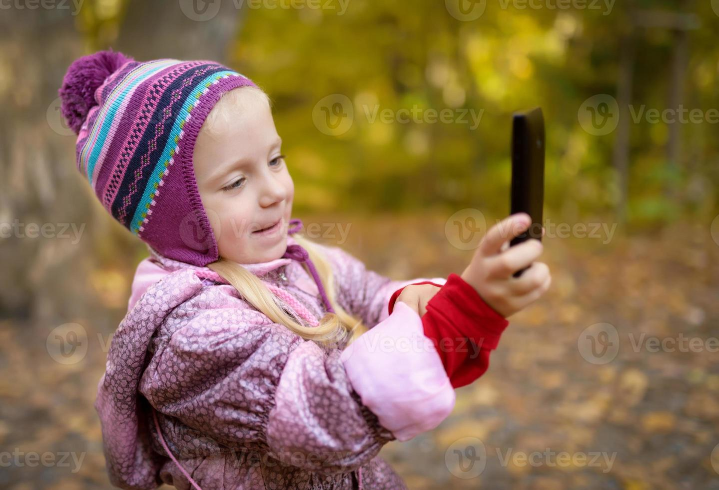 liten flicka att göra foto med smartphone.