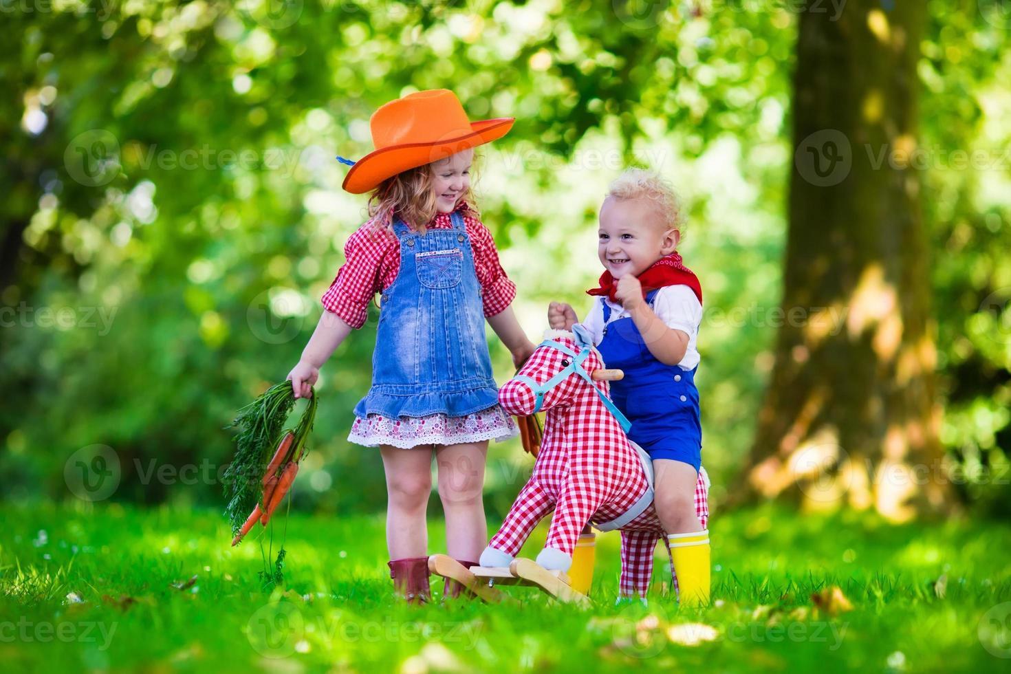 cowboybarn som leker med leksakshäst foto