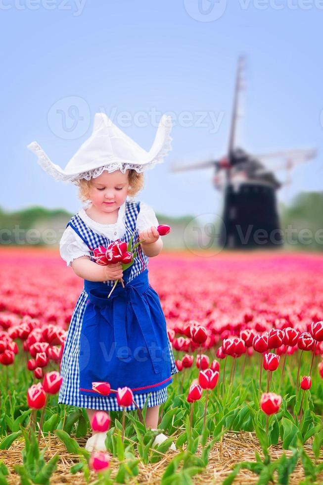 vacker flicka i holländsk dräkt på tulpanfält med väderkvarn foto