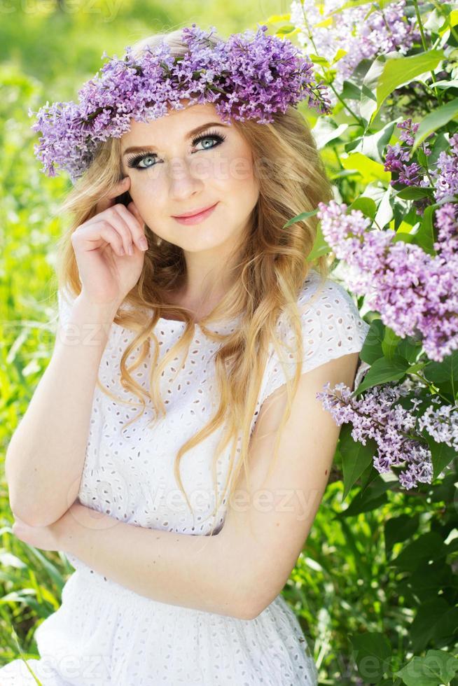 porträtt av vacker flicka med krans från lila blommor foto