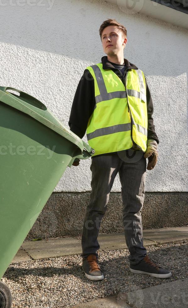 binman tar bort avfall - dra en grön avfallsbehållare foto
