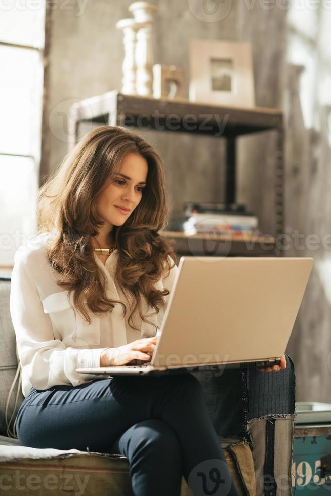 ung kvinna som använder bärbar dator medan man sitter i loftlägenhet foto
