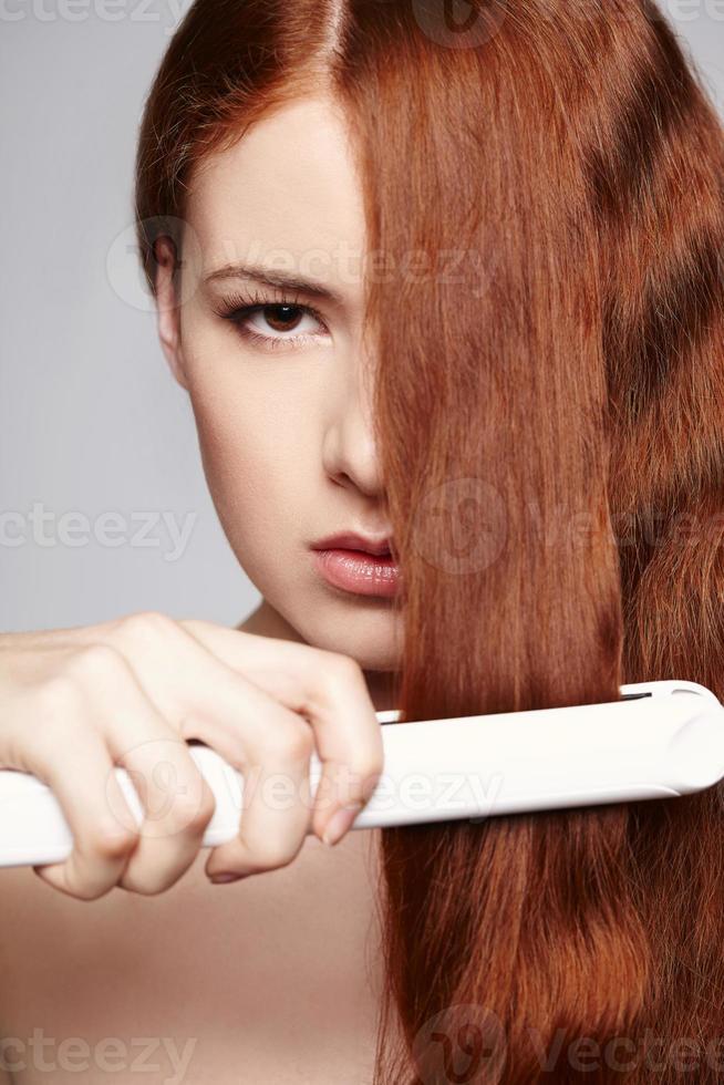 rödhårig kvinna med hårjärn foto