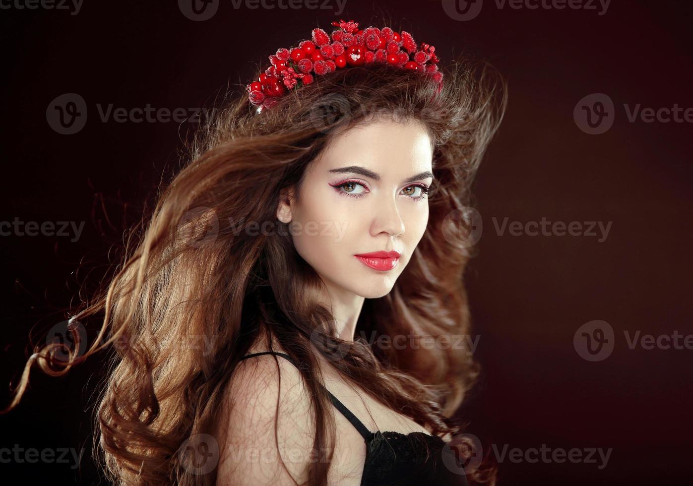 brunett ung kvinna med långt vågigt blåser hår och kapell foto