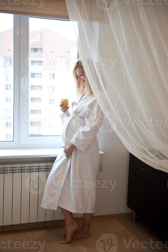 gravid nära fönster foto