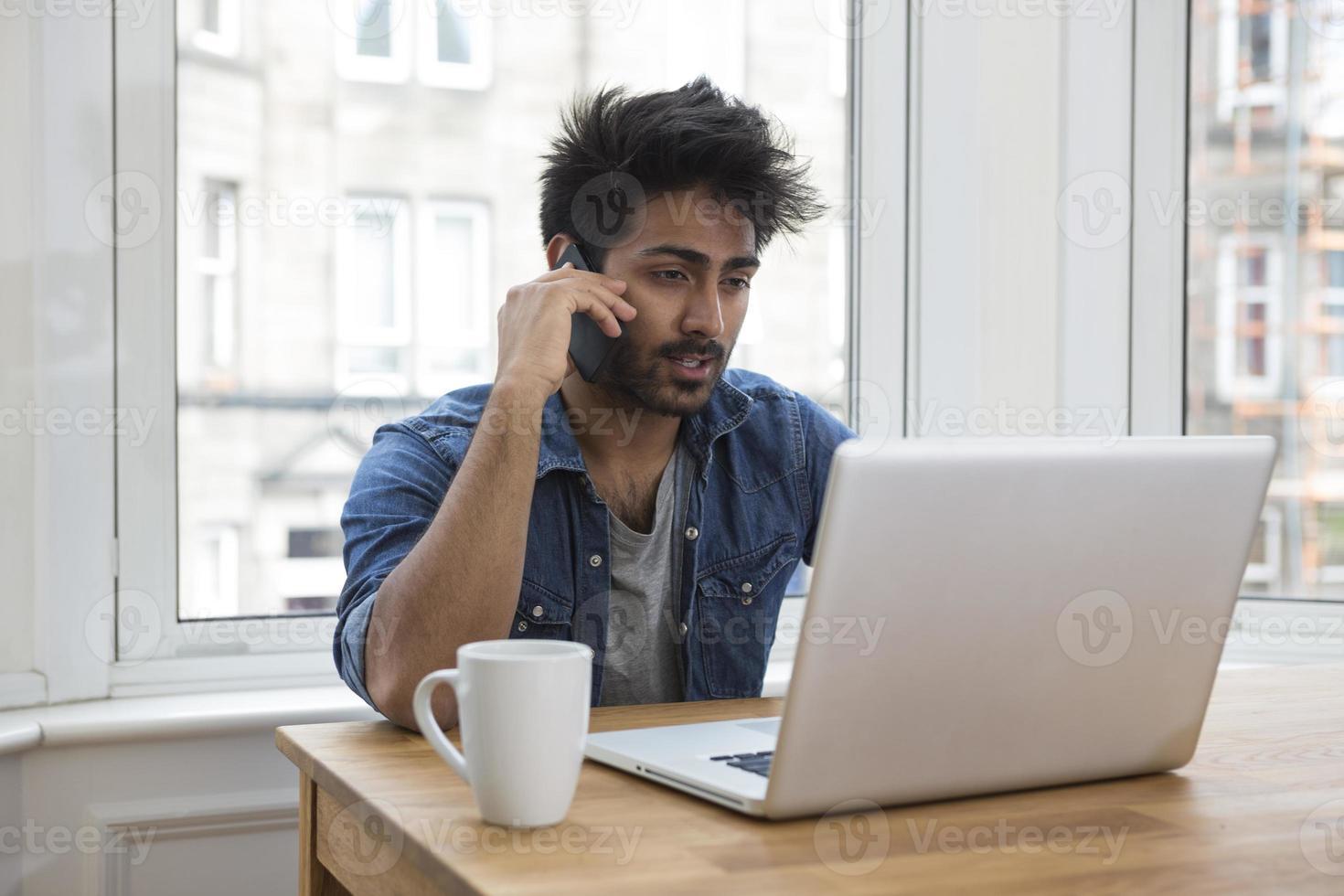 asiatisk man hemma arbetar på bärbar dator. foto
