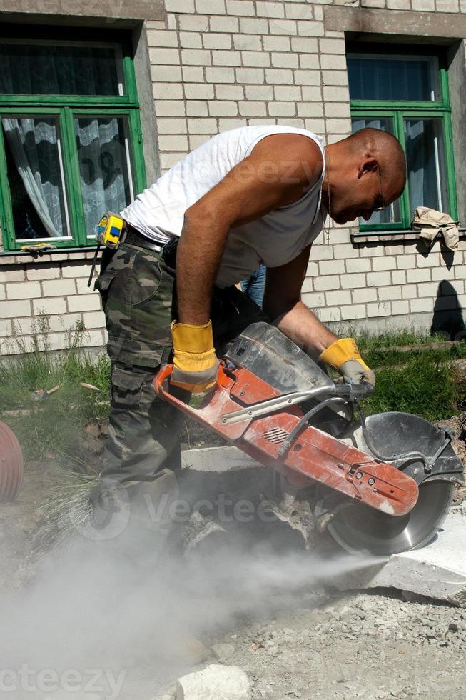 arbetare med industrisåg som skär en betongblock foto