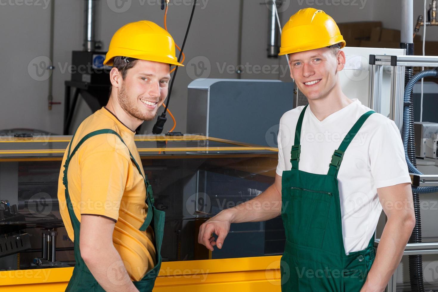 arbetare som står bredvid maskinen foto