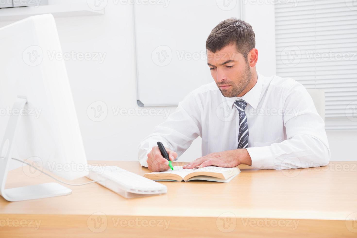 affärsman som sitter vid skrivbordet och läser en bok foto