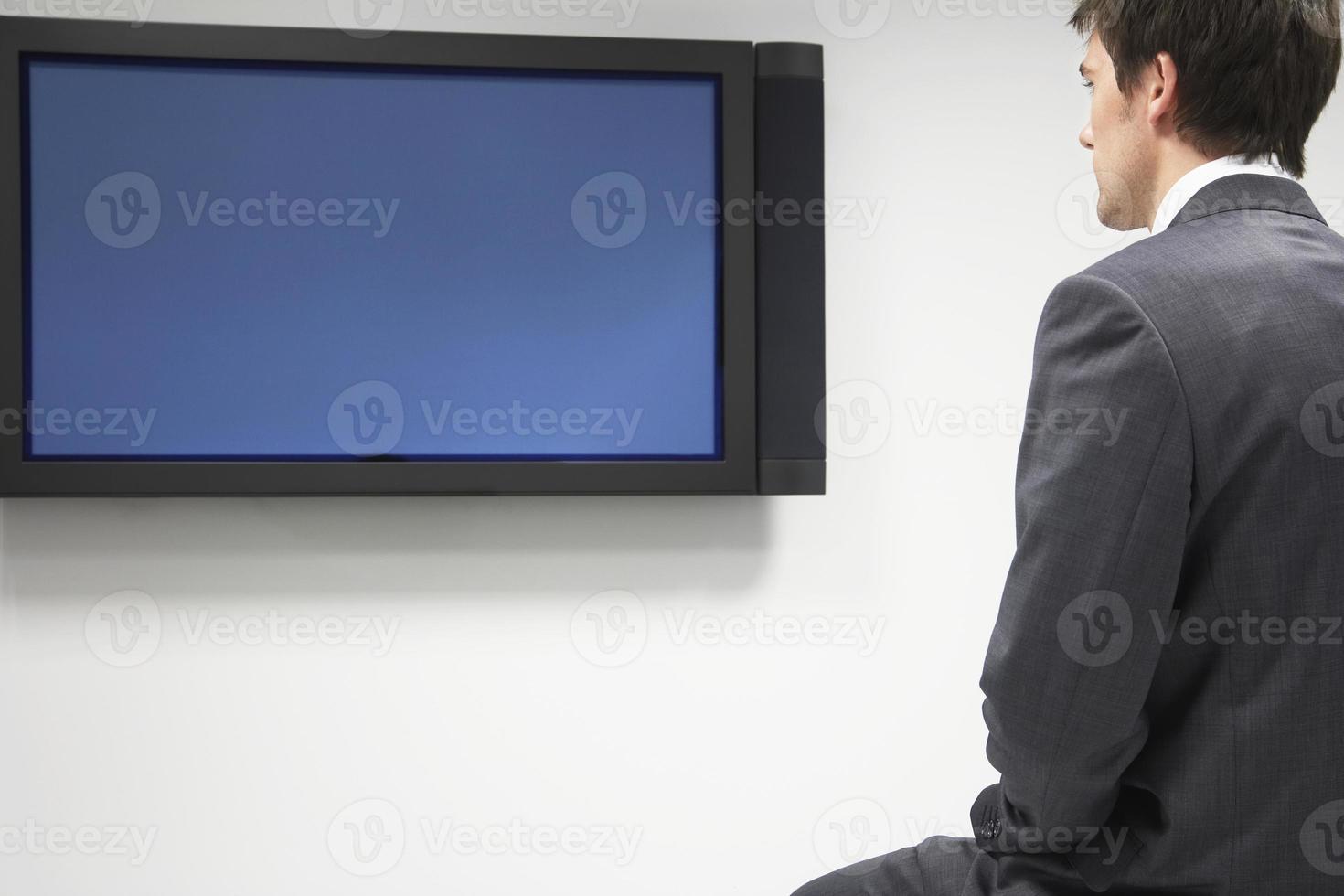 affärsman tittar på platt-TV foto