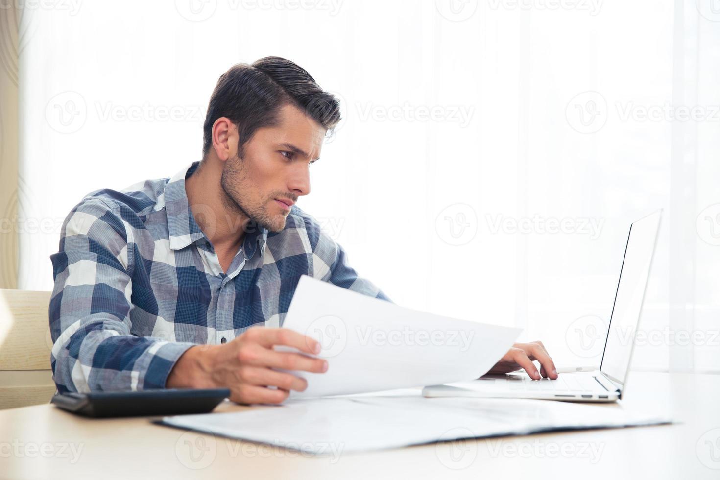 man sitter vid bordet med räkningar och bärbar dator foto