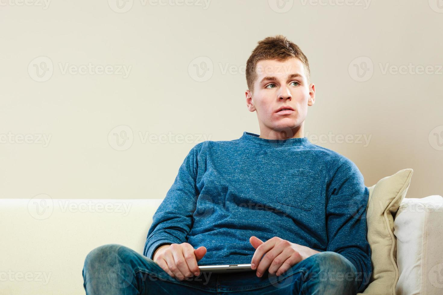 ung man med digital tablet sitter på soffan foto