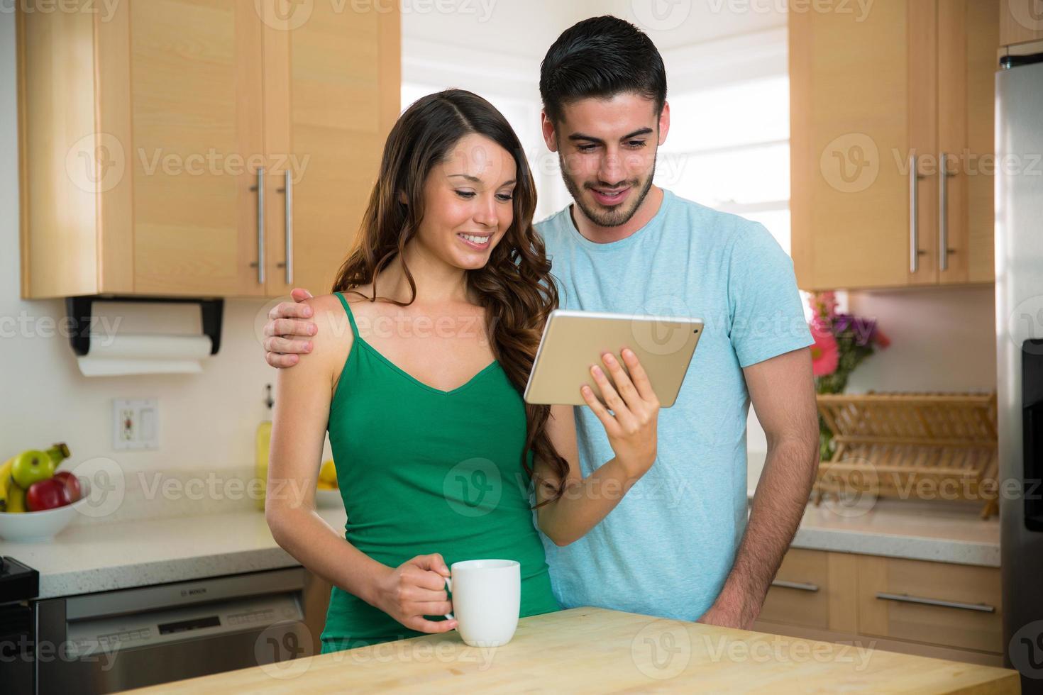 man och hustru tittar på familjefoton i modernt kök foto