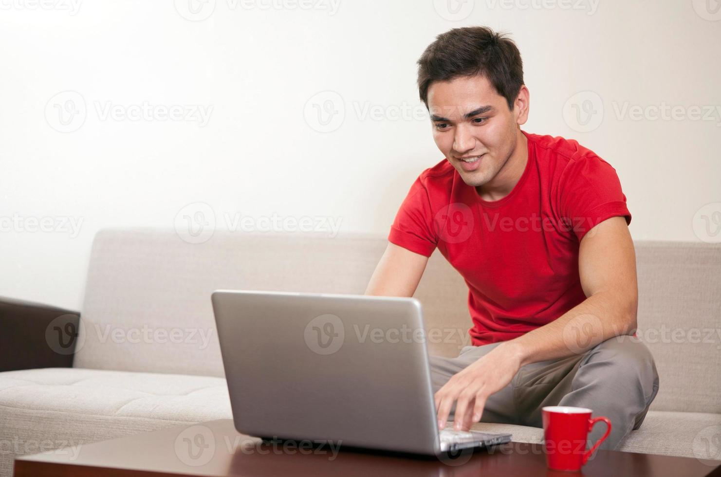 ung man som arbetar på en bärbar dator foto