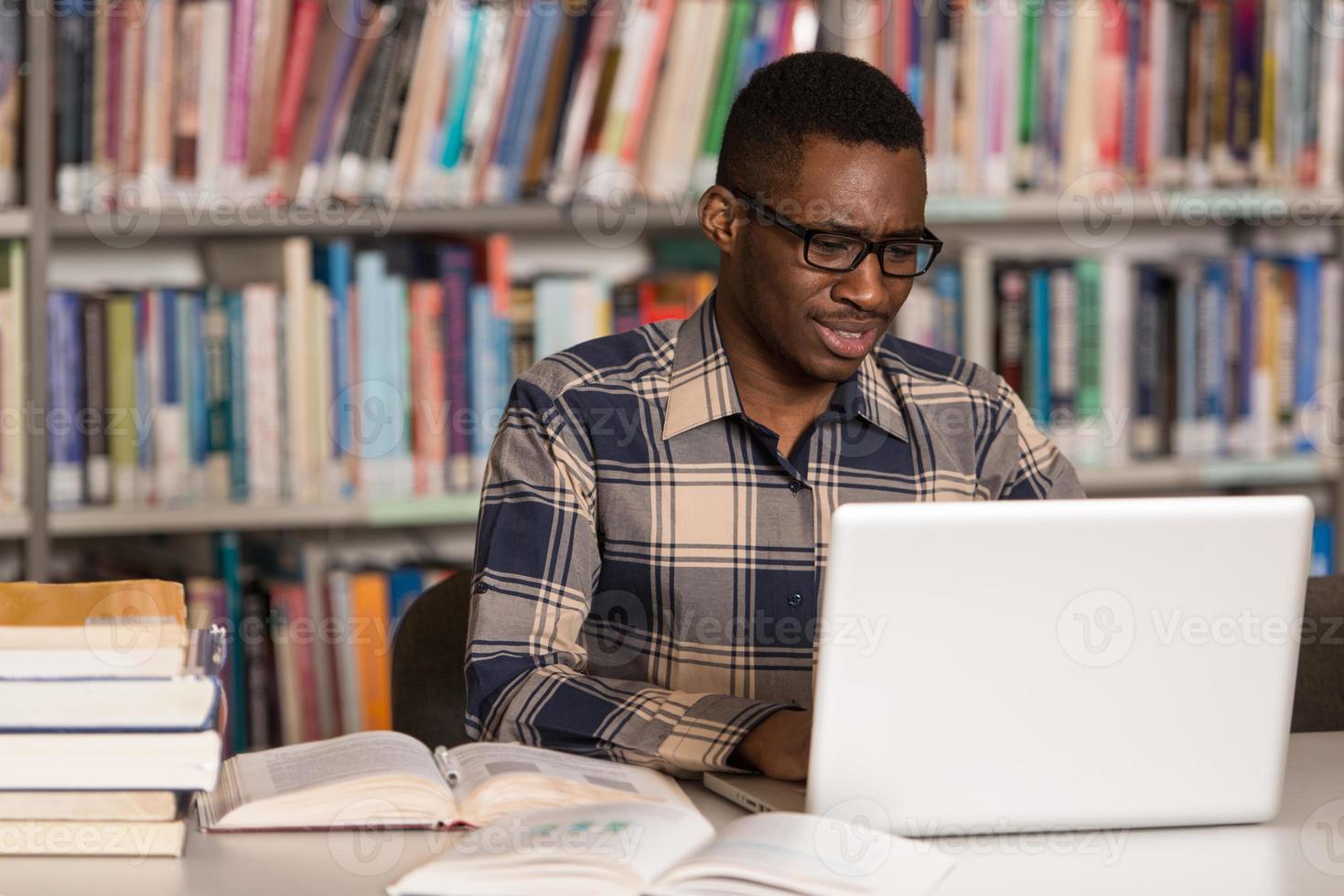 glad afrikansk manlig student med bärbar dator i biblioteket foto