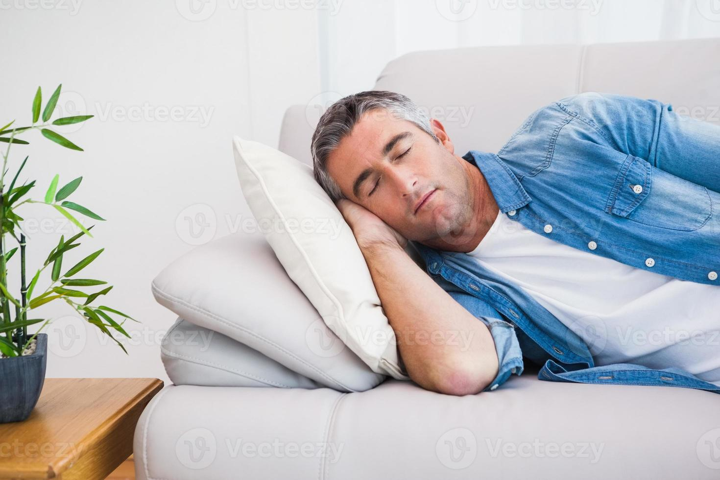 man med grått hår som sover i soffan foto