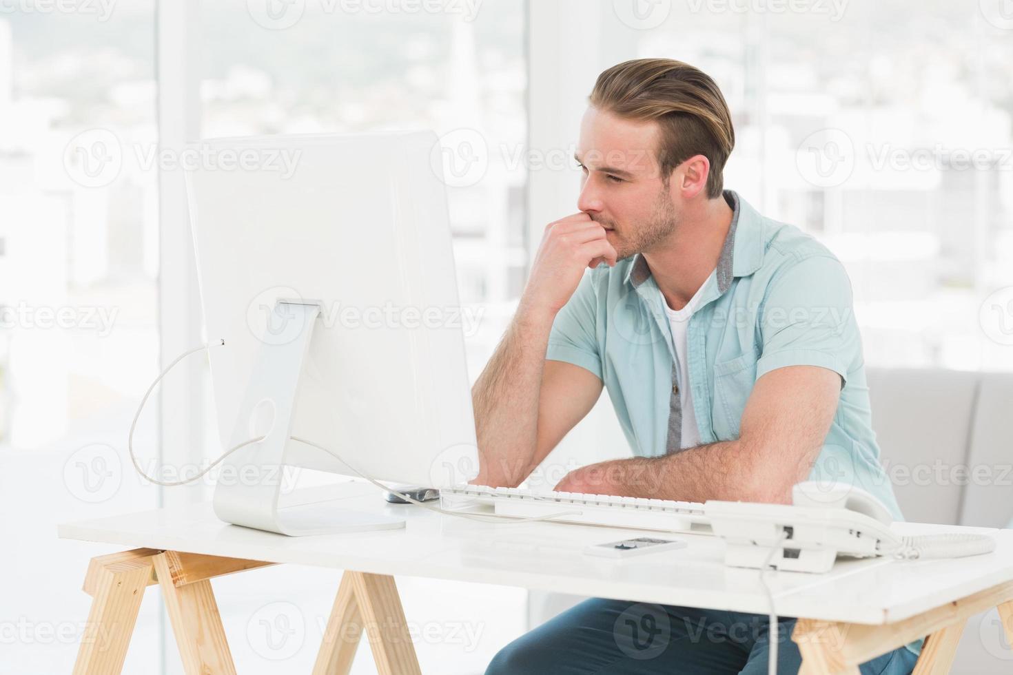 koncentrerad affärsman som arbetar med datorn foto