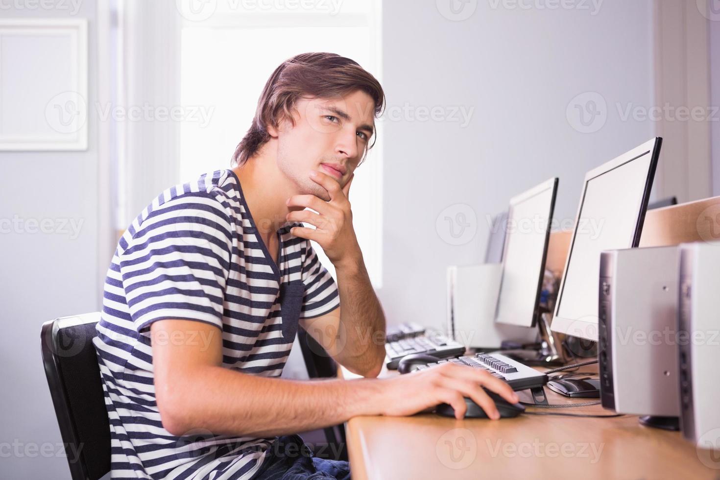 student som använder dator i klassrummet foto