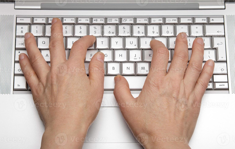 kvinnliga händer som skriver ut på knappsatsen en bärbar dator foto