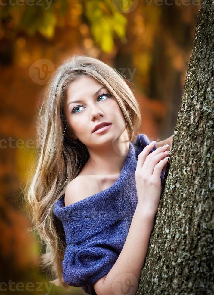 attraktiv kvinna som tillbringar tid i parken under höstsäsongen foto