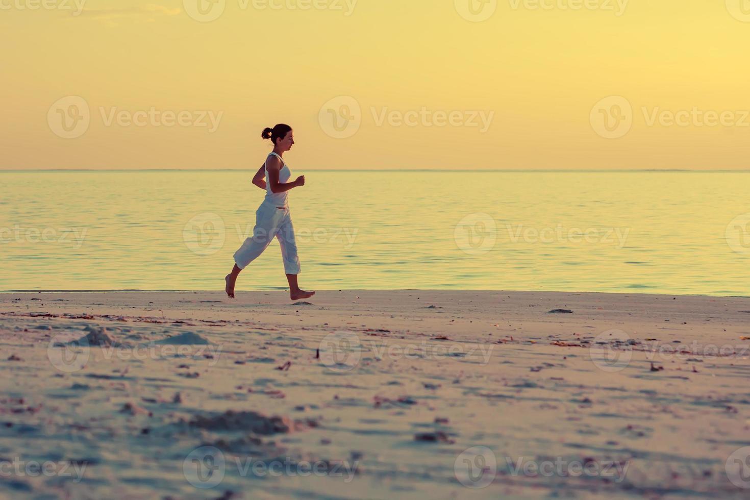 kaukasisk kvinna som joggar på stranden foto