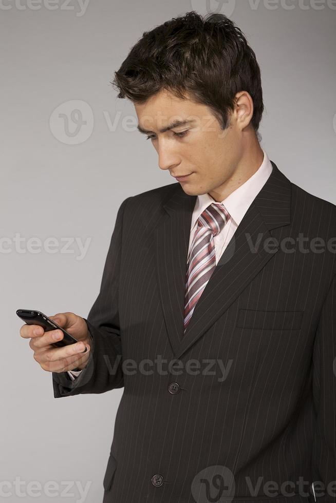 ung kaukasisk affärsman som leker med telefonen foto
