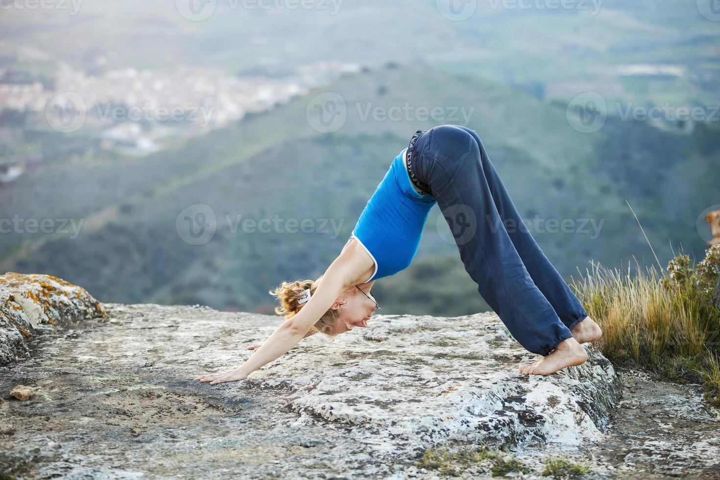 kaukasisk kvinna som utför nedåtriktad hundyoga foto