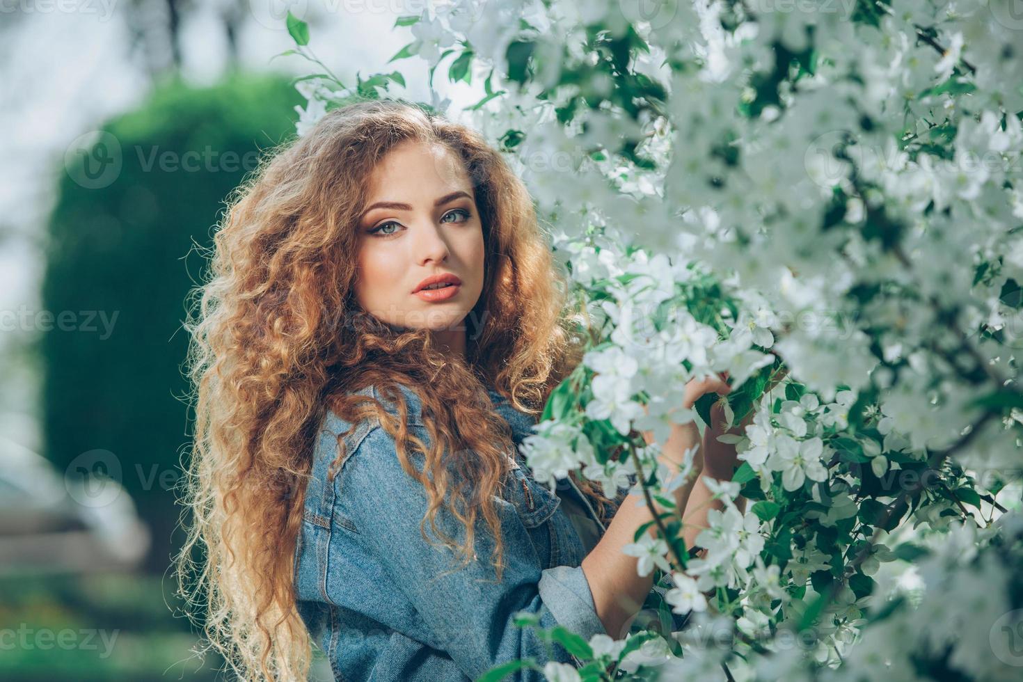 vacker ung kaukasisk flicka med lockigt hår utomhus foto