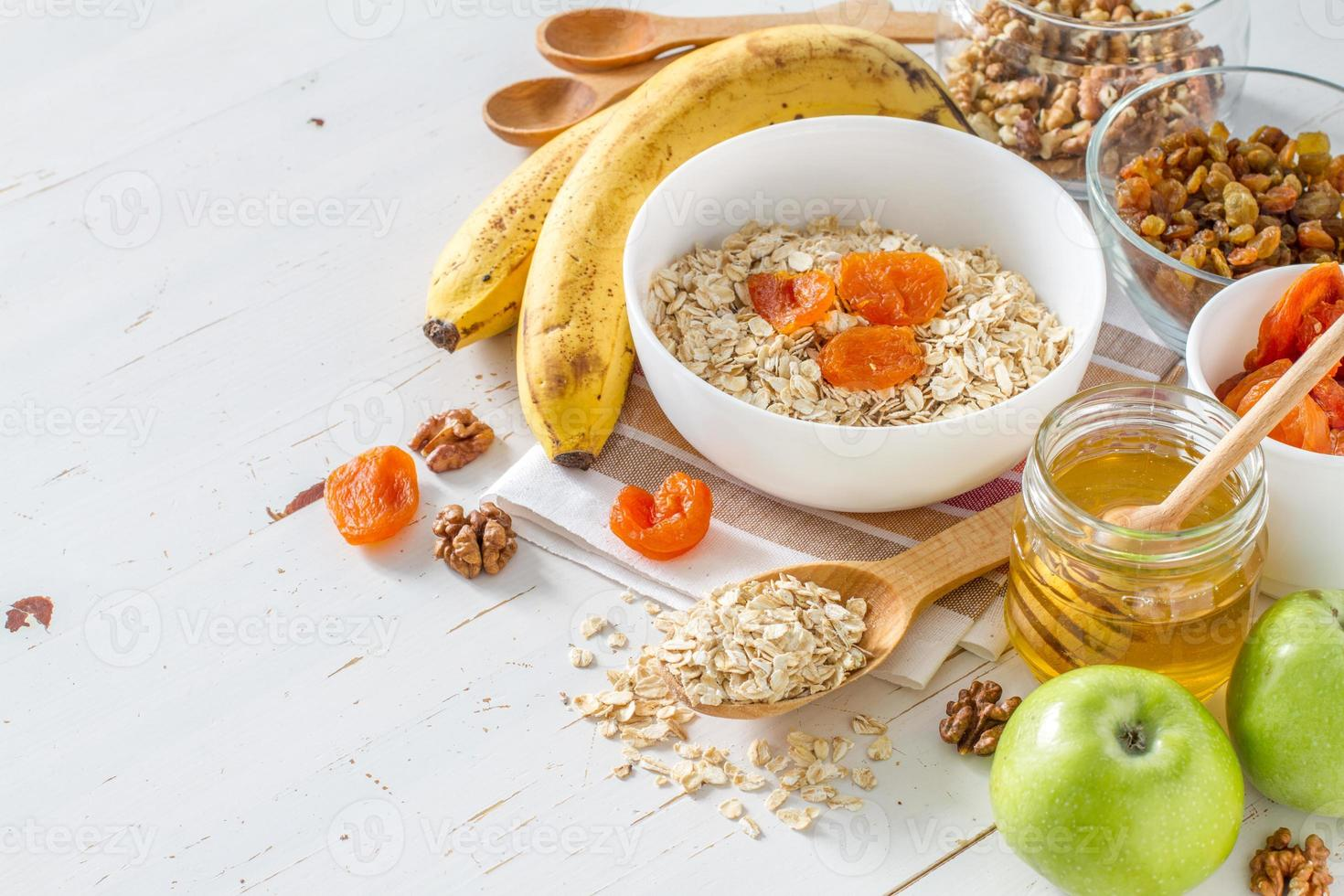 granola ingredienser - havre, banan, honung, nötter, äpple, torkad aprikos foto