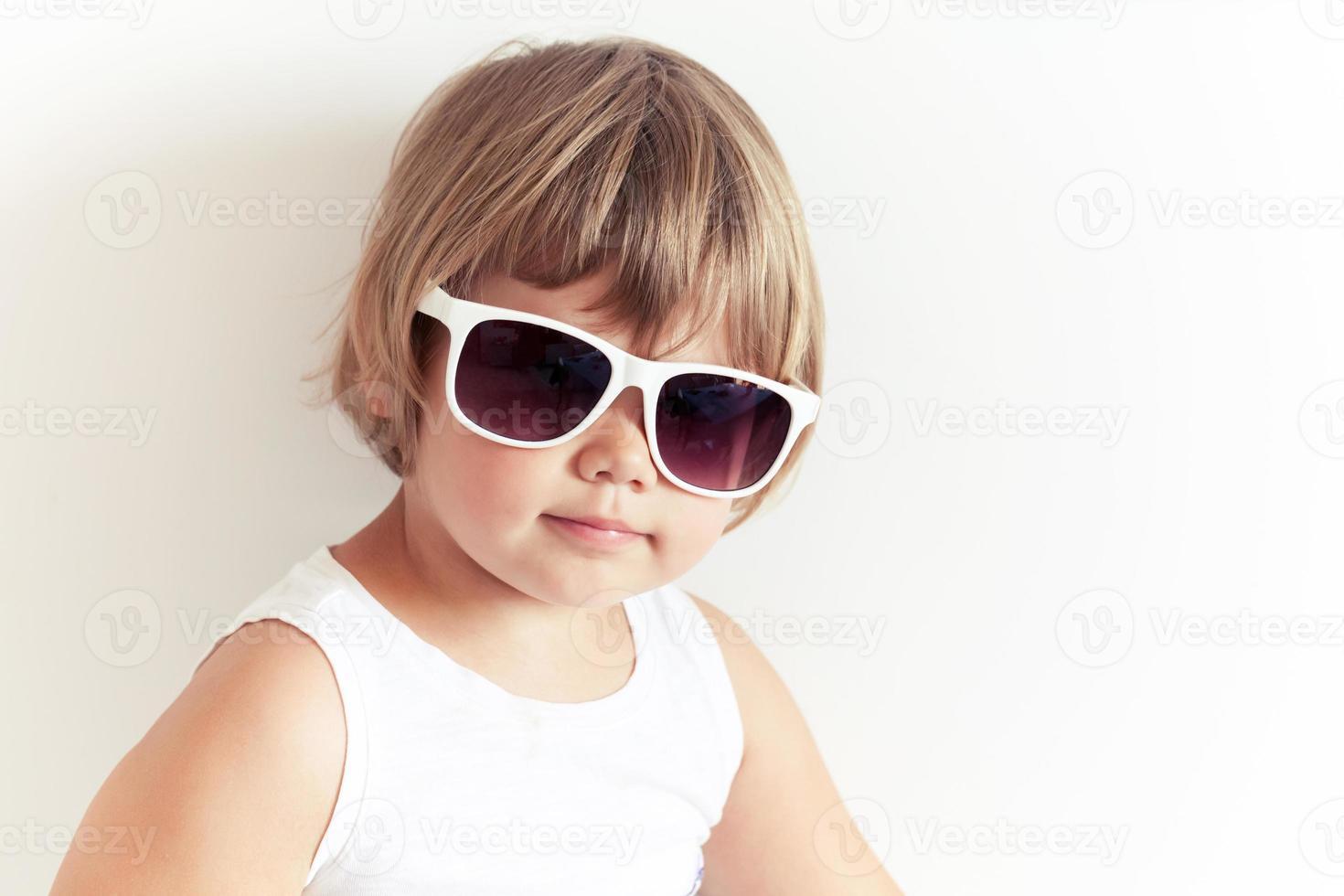 söt kaukasisk liten flicka i solglasögon på vitt foto