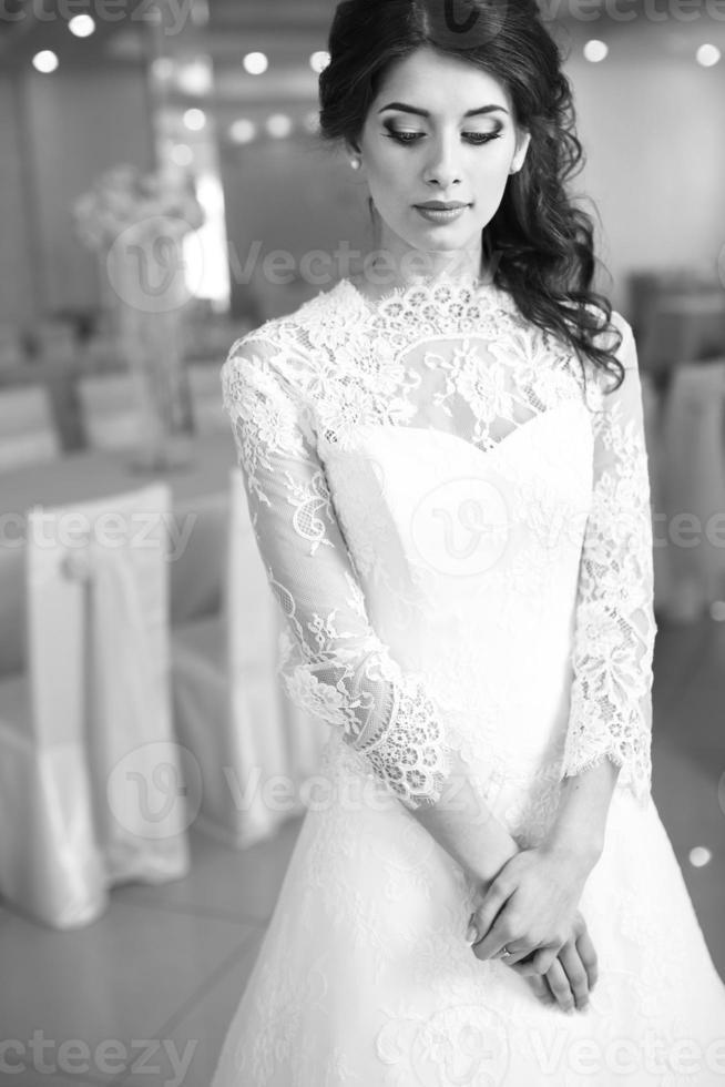 vacker ung kaukasisk brud i trendig bröllopsklänning. foto