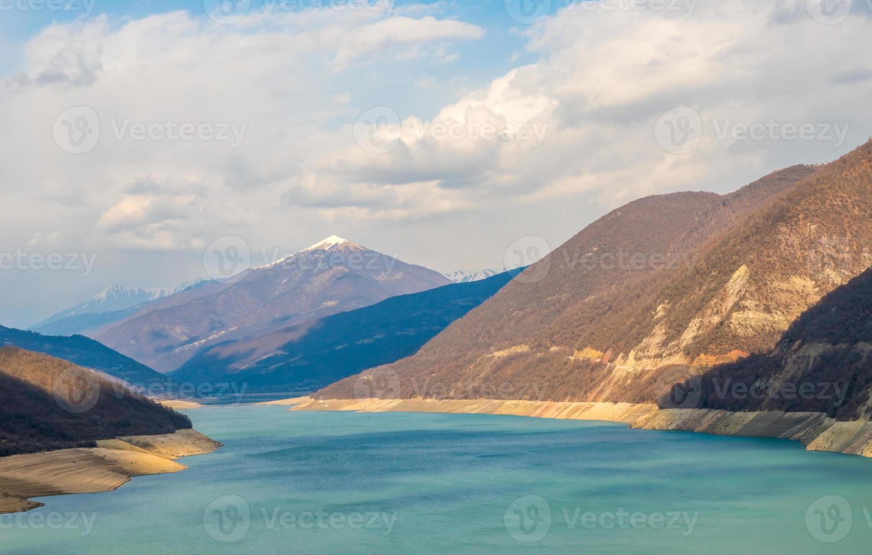 kaukasiska berg nära den gröna sjön och fantastiska moln foto