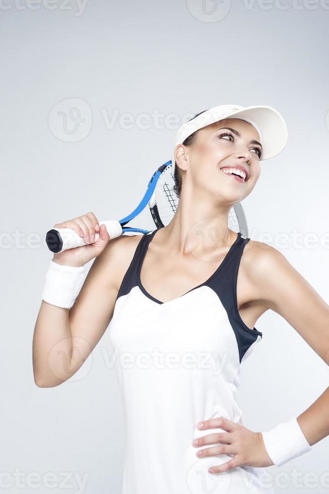 tennisbegrepp: porträtt av glad ung kaukasisk kvinnlig tennis foto