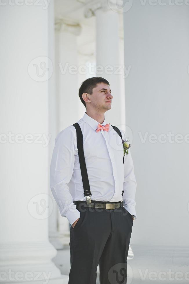 brudgum på bakgrunden av vita kolumner foto